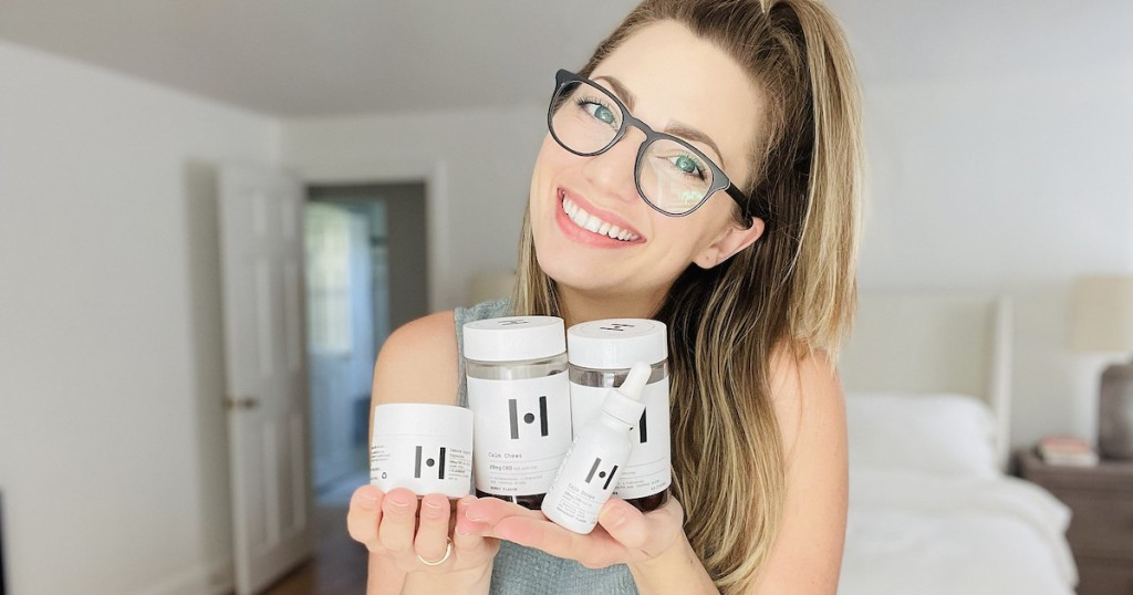 woman holding cbd pill bottles smiling