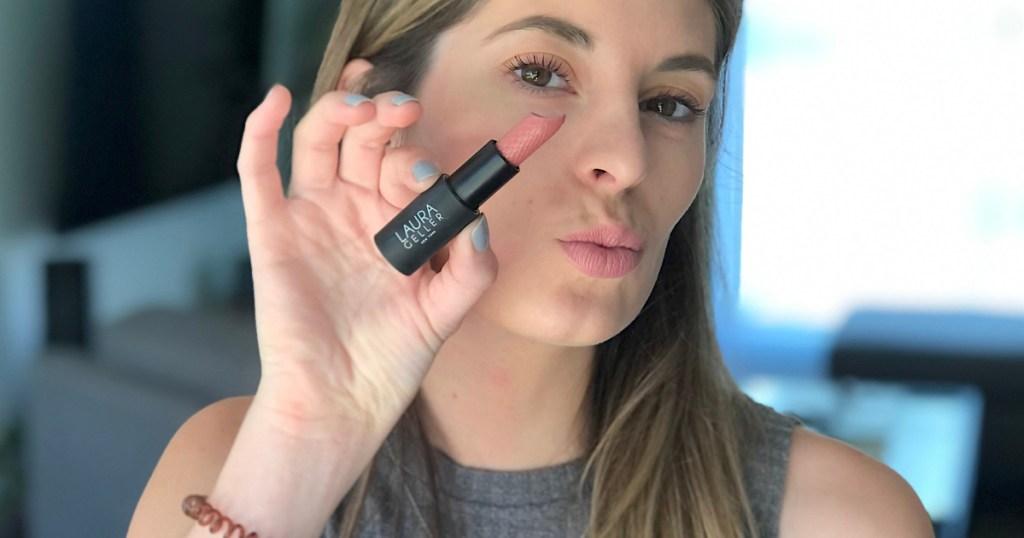 woman holding a laura geller liptstick