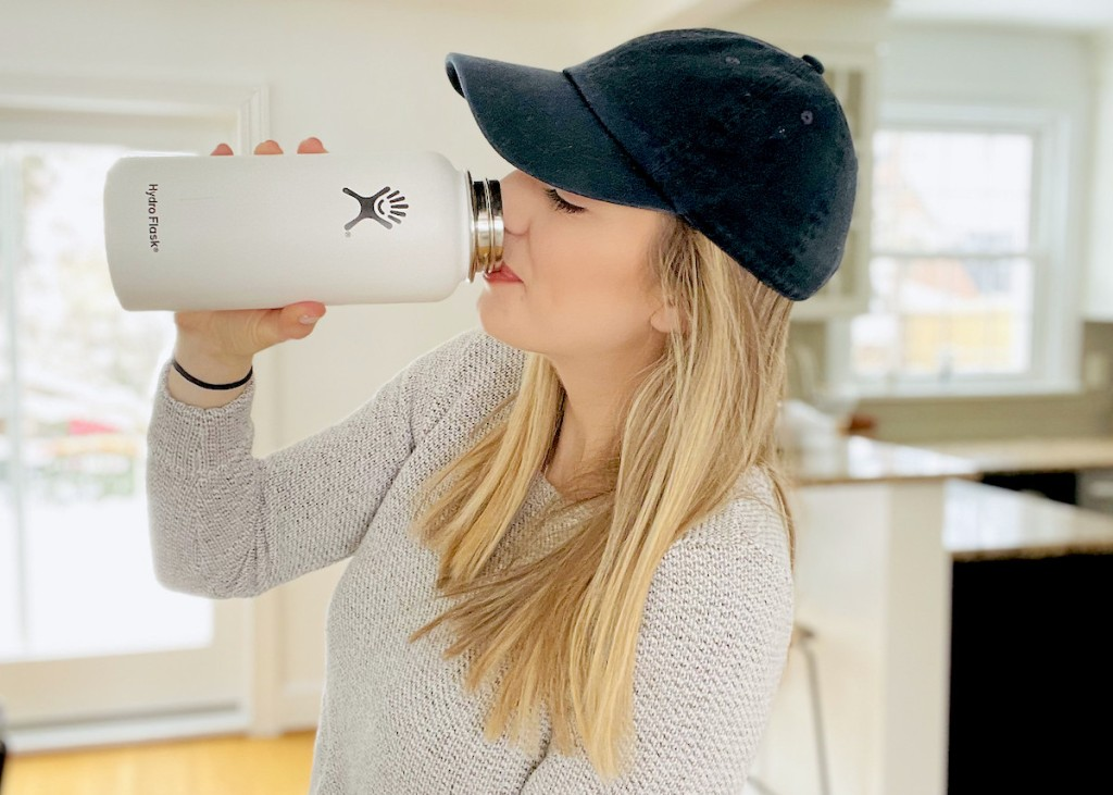 woman drinking out of white hydroflask water bottle