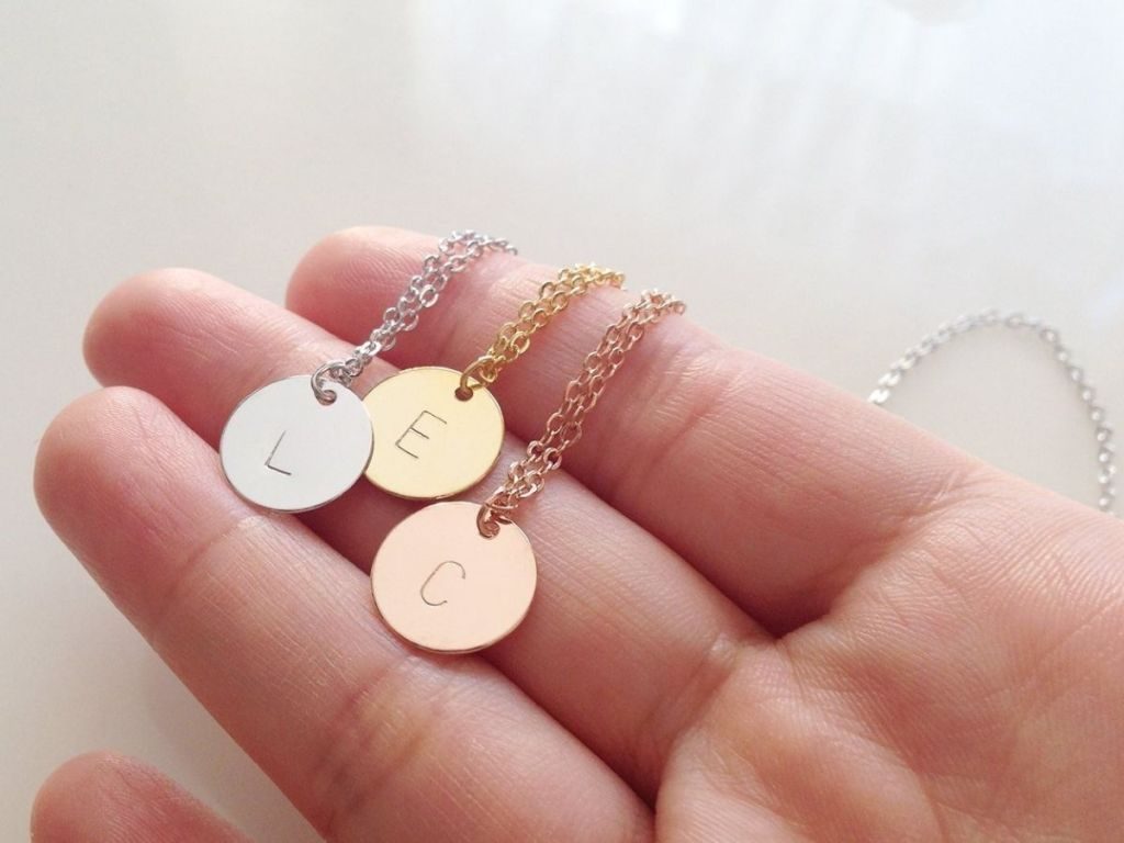 hand holding initial stamped necklace charms