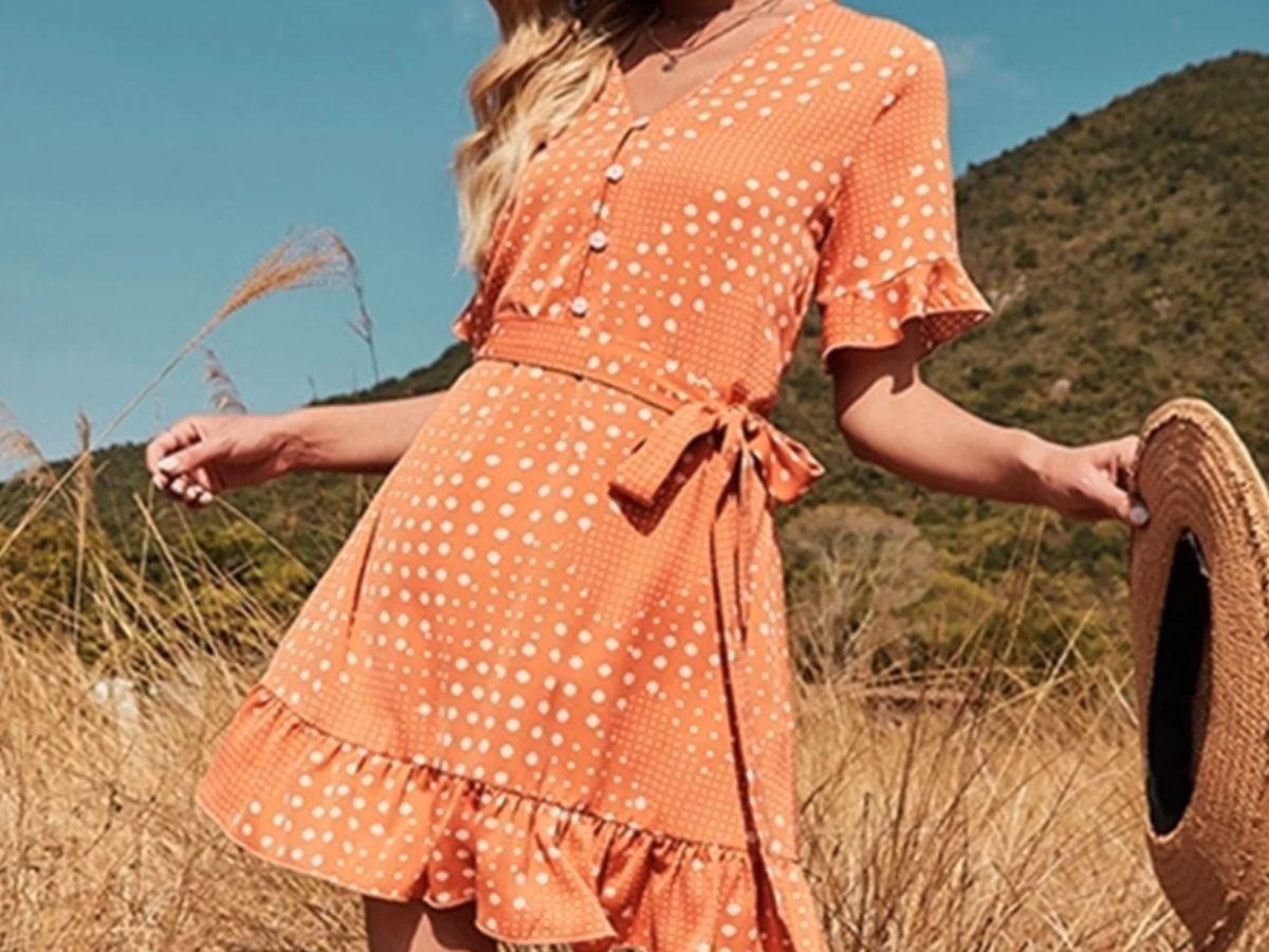 woman in field wearing orange and white polka dot dress