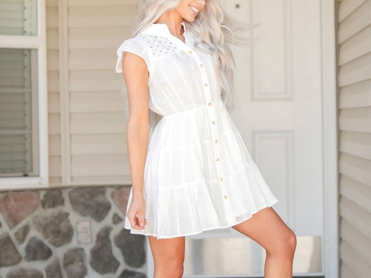 woman wearing white short dress with buttons down the front