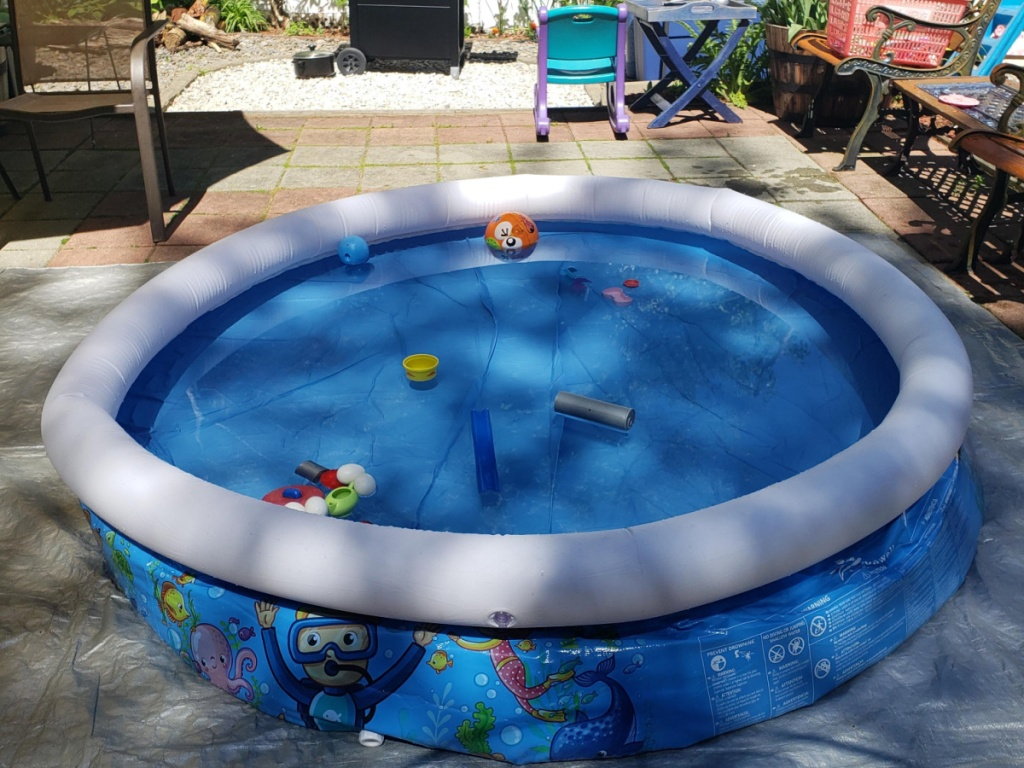 colorful inflatable pool with water toys in it