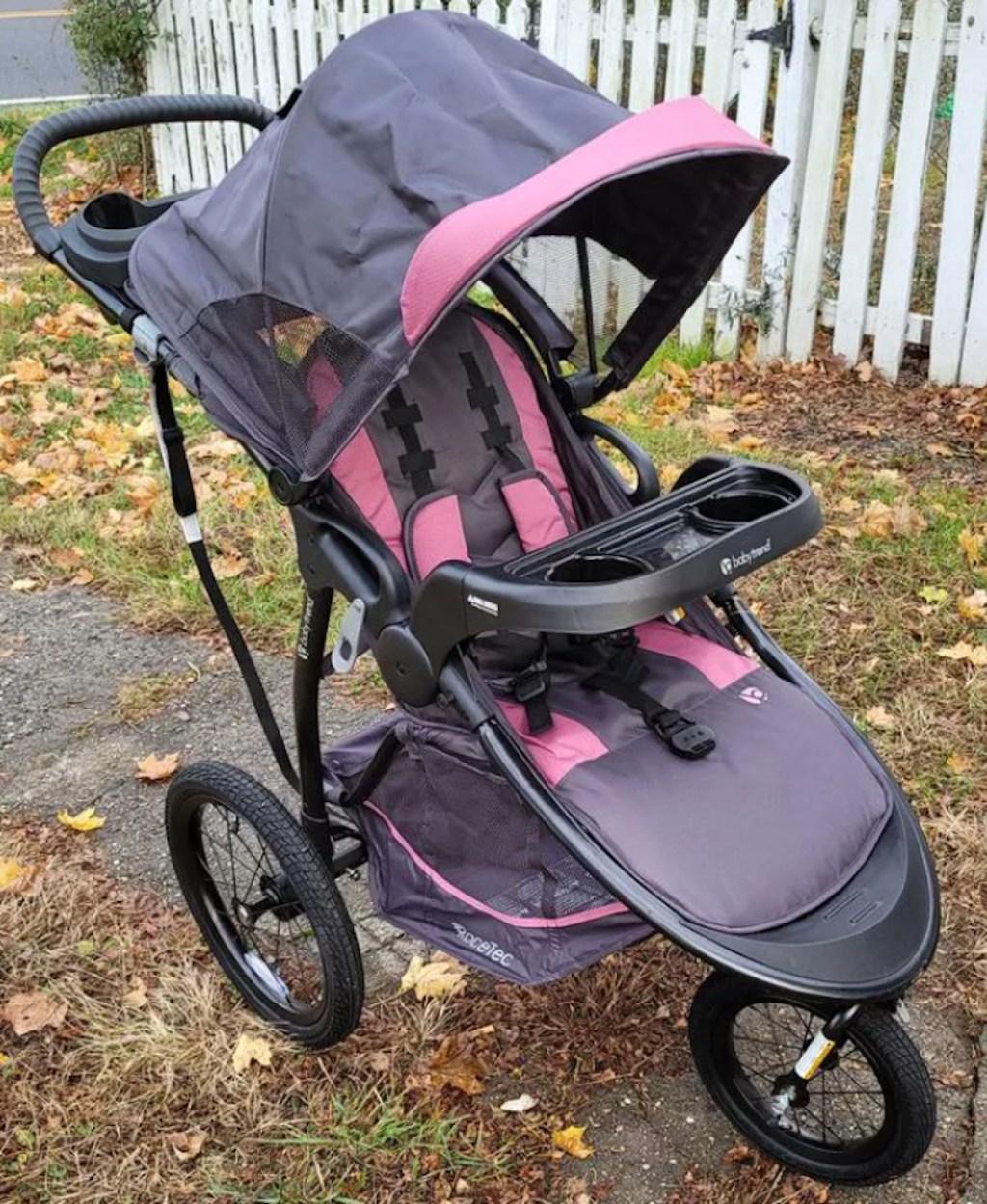 pink and gray jogging stroller outside on sidewalk