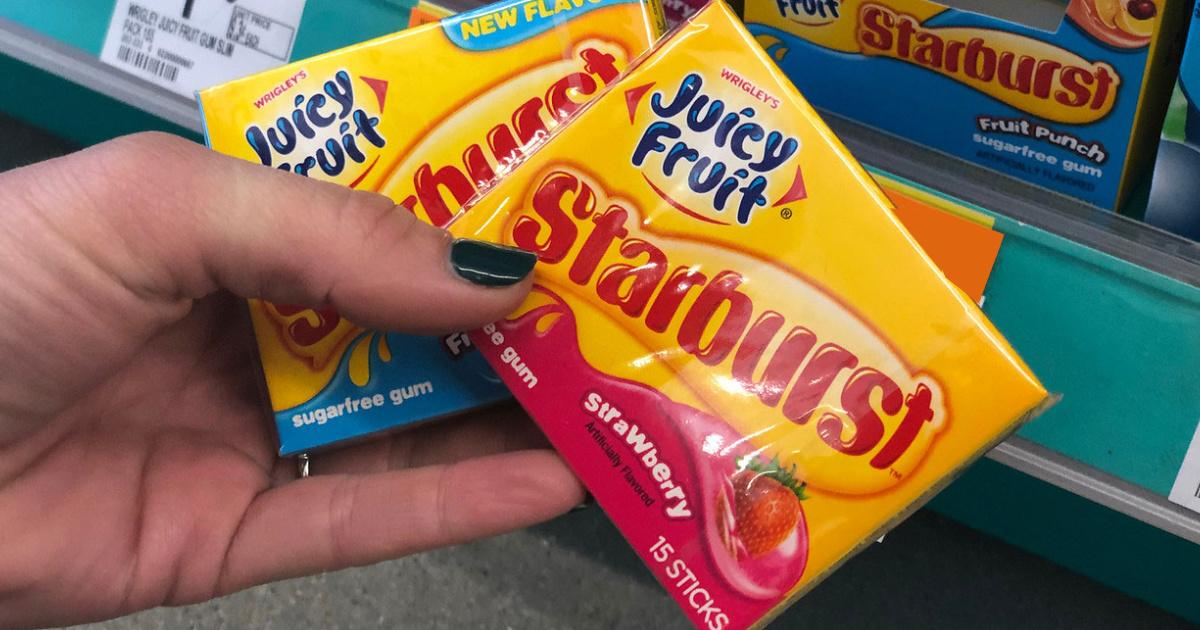 hand holding two packs of juicy fruit starburst gum