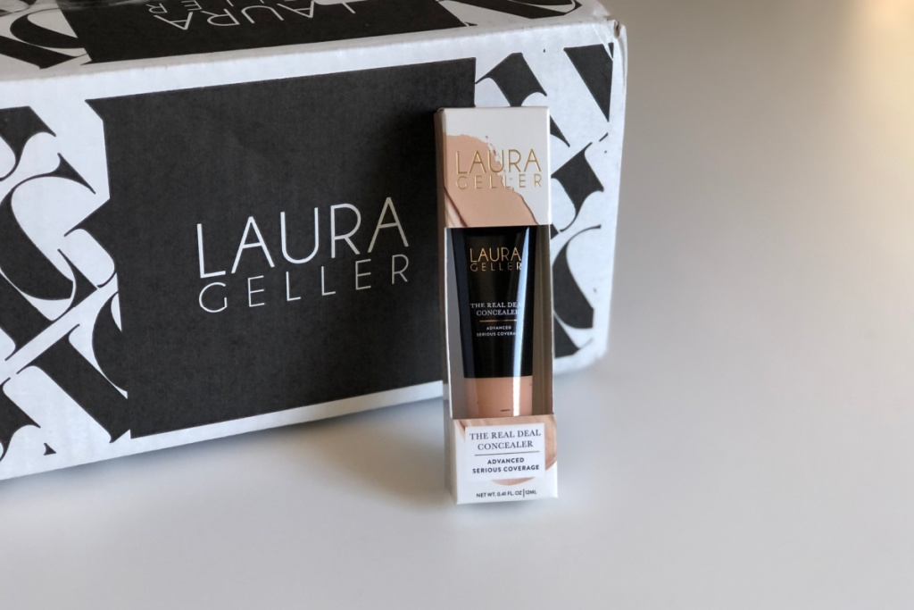 tube of laura geller makeup concealer on table next to box