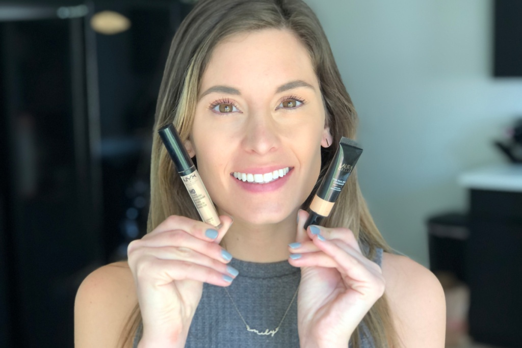 woman holding two NYX and laura geller concealers
