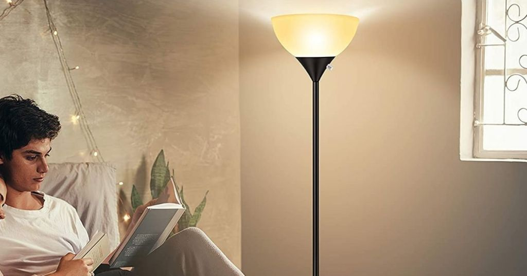 person reading in front of black floor lamp