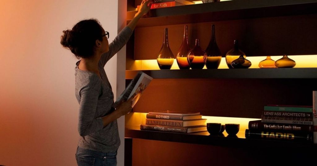 woman standing in front of backlit shelf