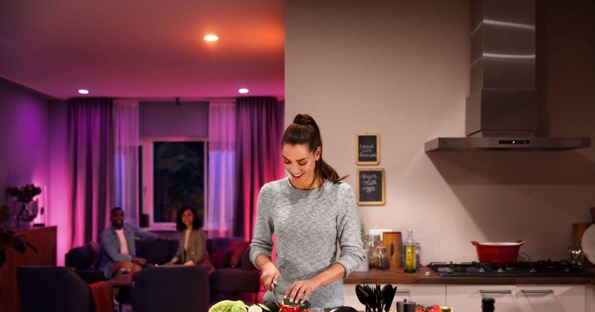 woman cutting veggies below colorful ceiling lights