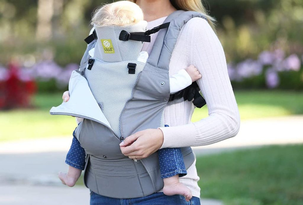 woman holding baby with gray baby carrier outside