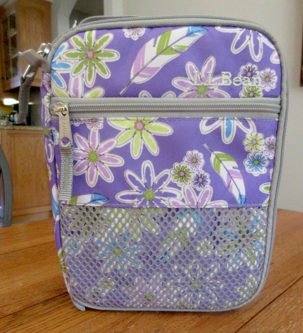 close up of purple flower ll bean kids lunchbox standing on wood table