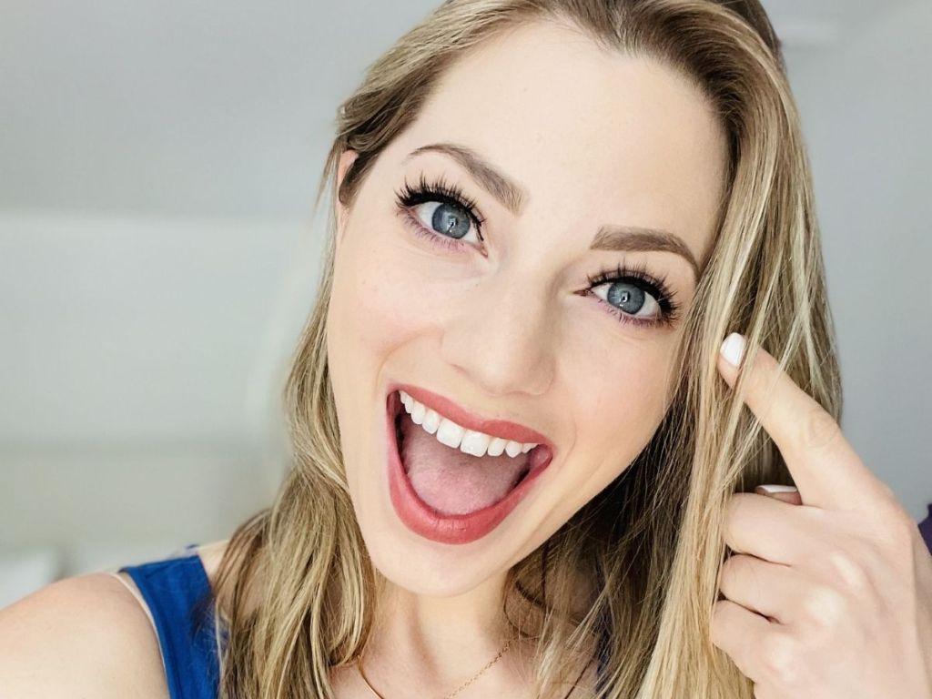 woman wearing fake eye lashes pointing to her eyes