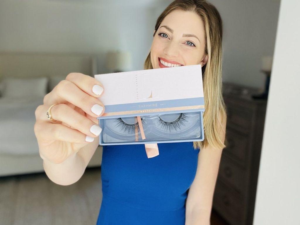 woman holding up pack of false eye lashes