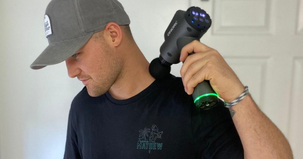 man using massage gun on neck