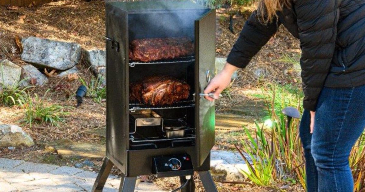 hand opening a smoker filled with meat