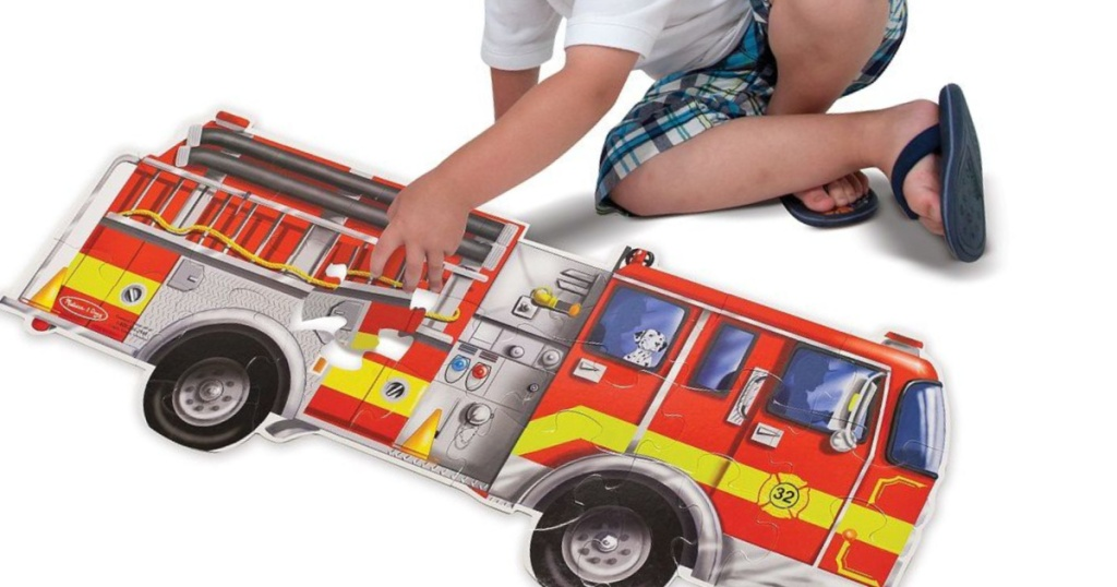 boy next to melissa & doug firetruck floor puzzle