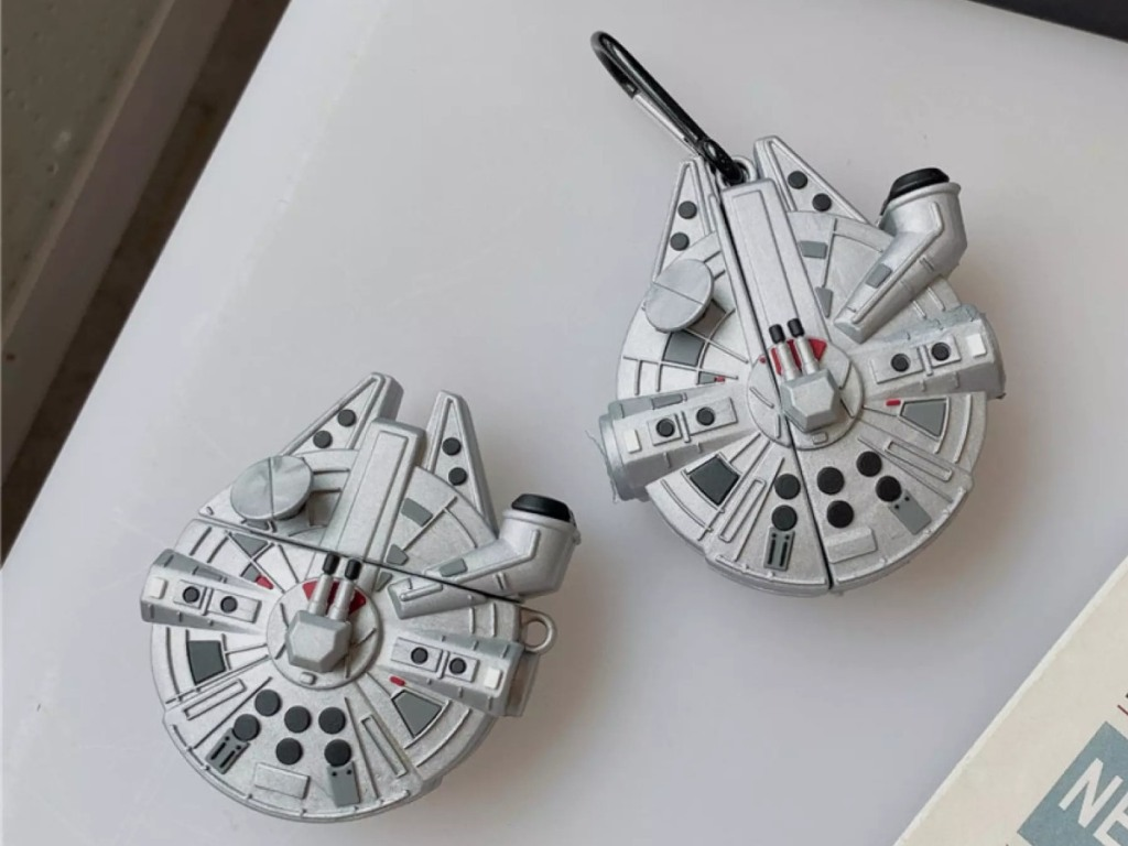 2 AirPods cases, both shaped like the Millenium Falcon