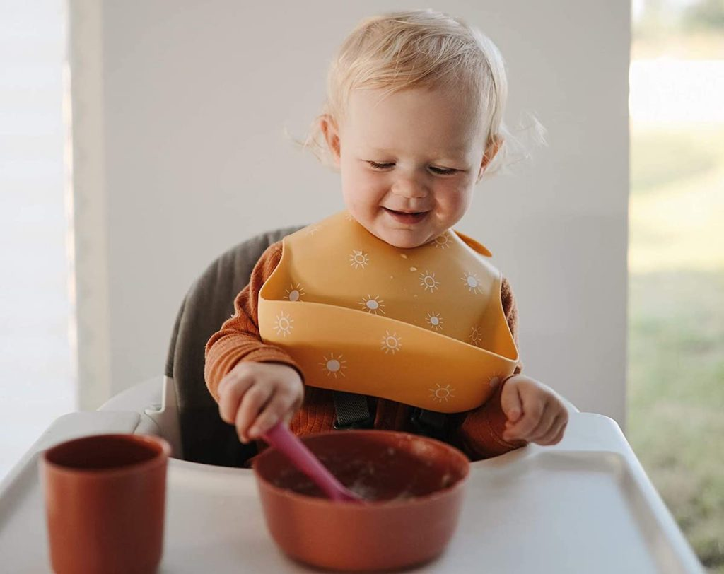 toddler sitting in highchair with yellow silicone bib eating out of bowl
