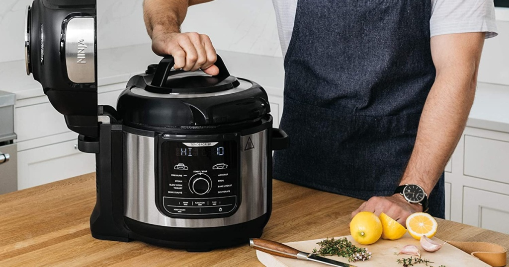 man remving lid from a large pressure cooker