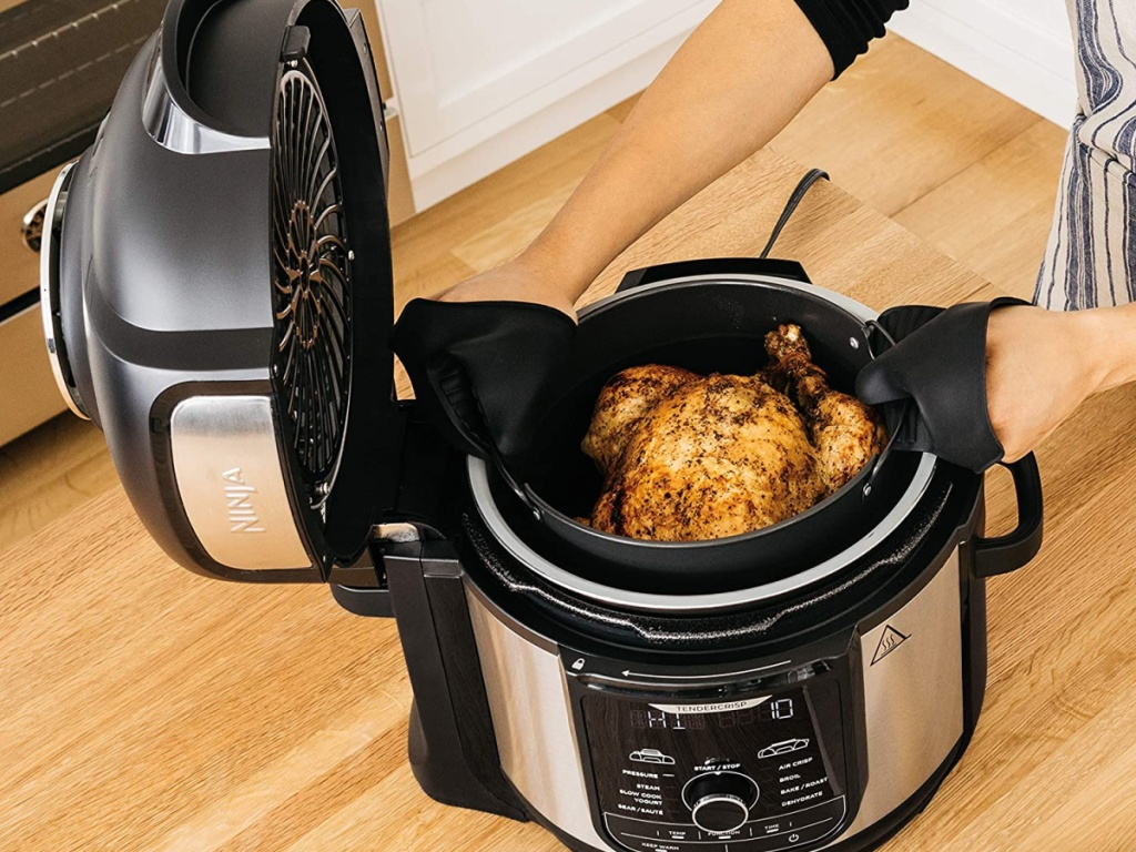 woman next to a large air fryer with a chicken in it