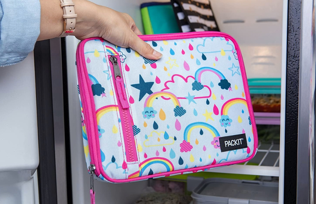hand holding a rainbow lunchbox in front of open refrigerator