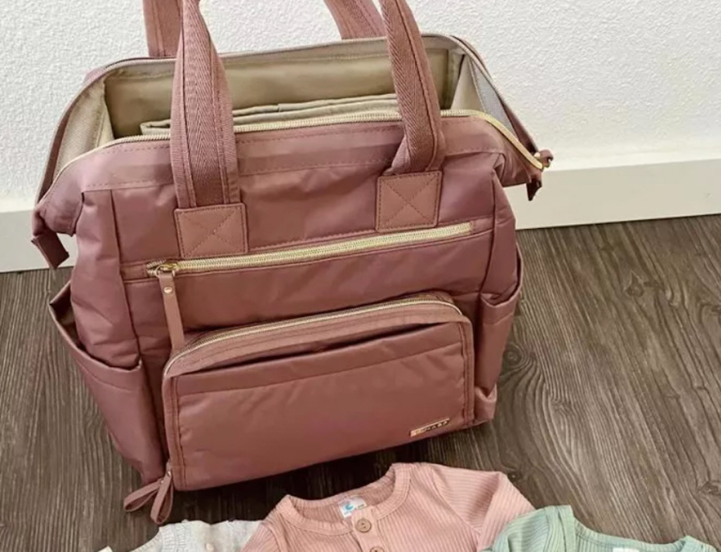 must have pink diaper bag sitting on wooden floor