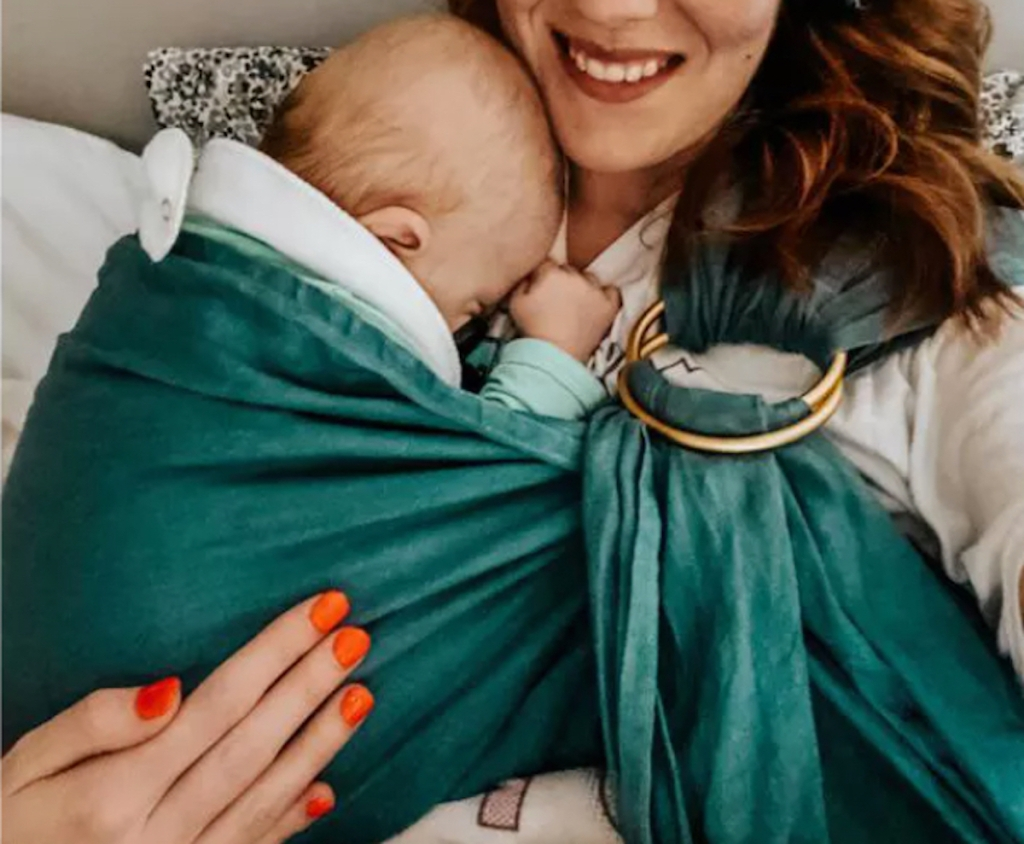 woman holding baby in emerald green ring sling