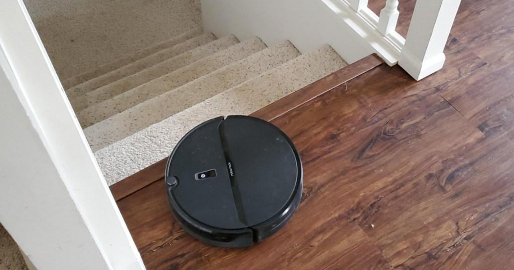 black robot vacuum near stairs