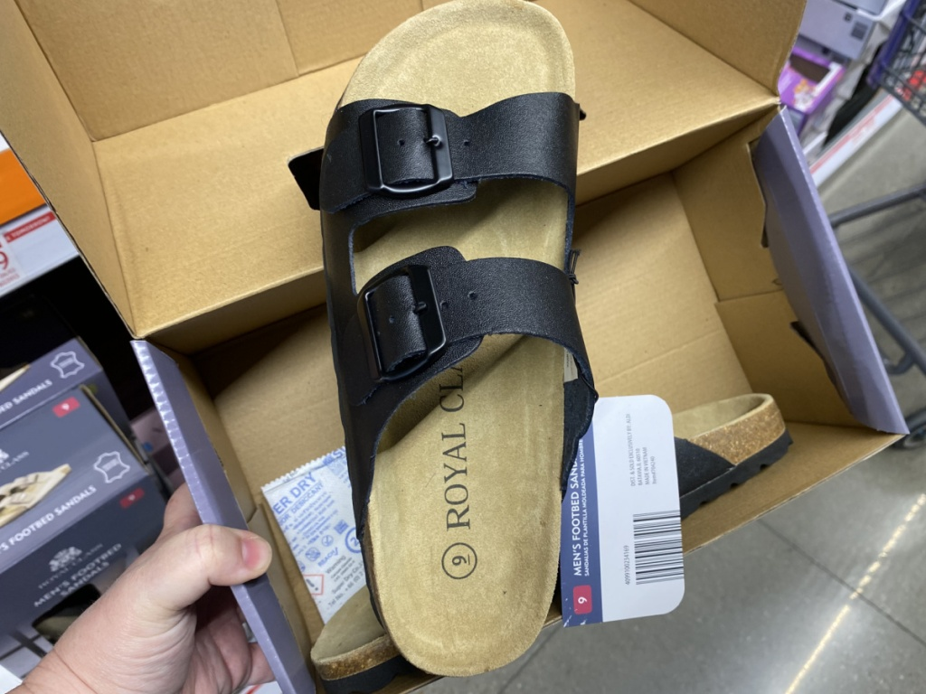 hand holding open box with man's sandal in it