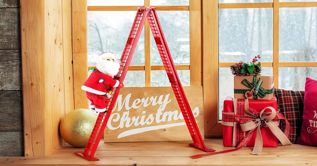Santa walking a red ladder on a shelf by a window with other Christmas decorations
