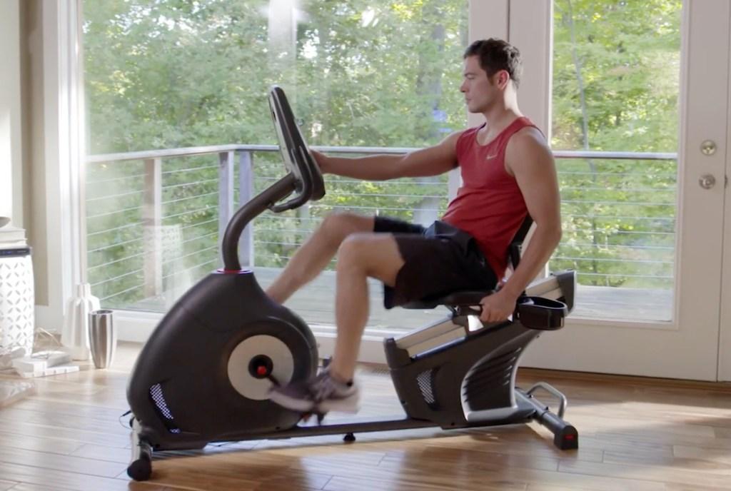 man sitting on exercise bike in room full of windows