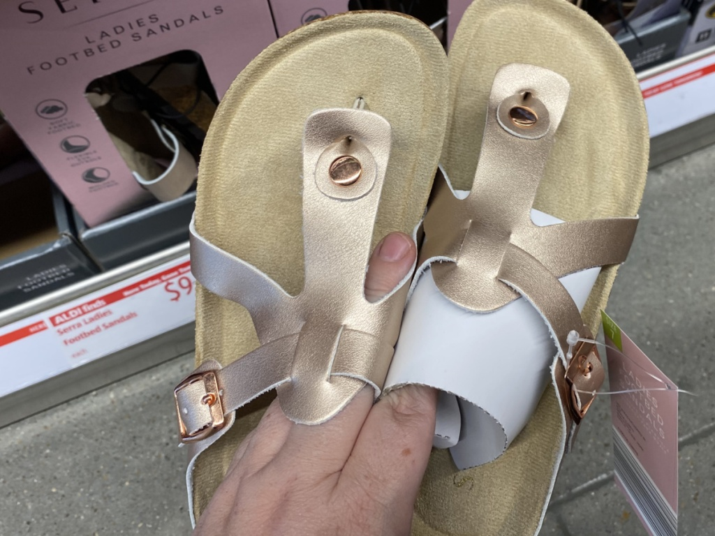 hand holding up gold pair of sandals in store