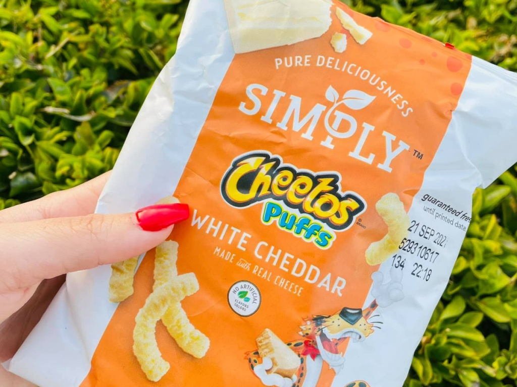 hand holding Simply Cheetos puffs