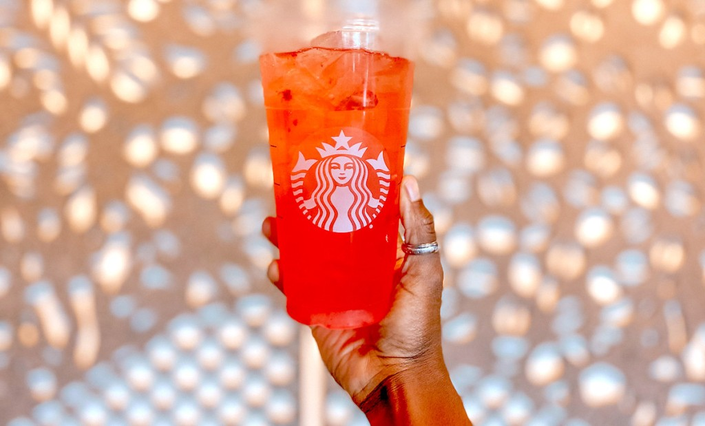 hand holding up a red colored starbucks iced gummy bear drink with lights on wall in background