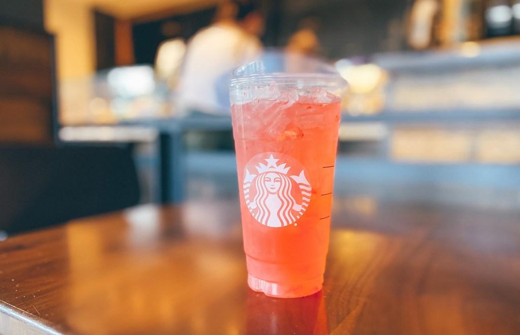 orange pink drink in starbucks cup on wood table