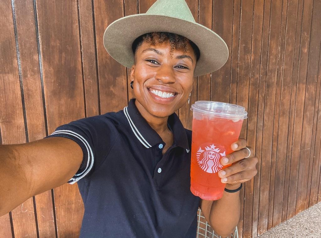 woman holding starbucks gummy bear secret menu drink smiling