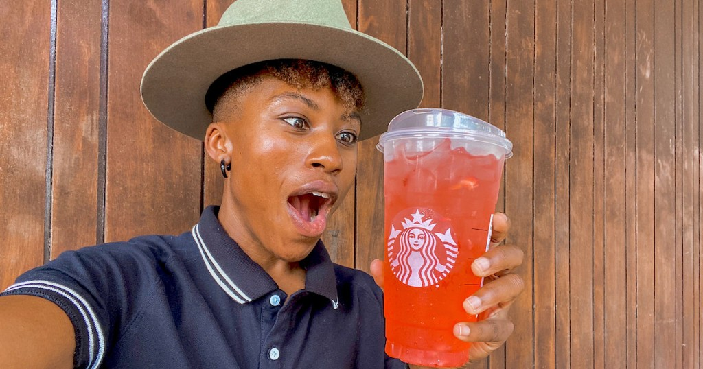 woman with mouth open staring at pink drink in starbucks cup