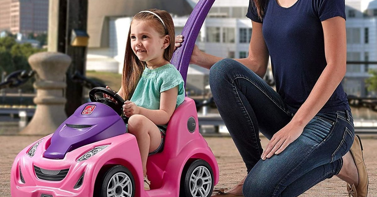 young girl being pushed in a toy car
