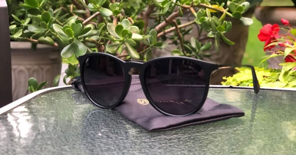 black sunglasses resting on cloth on glass table