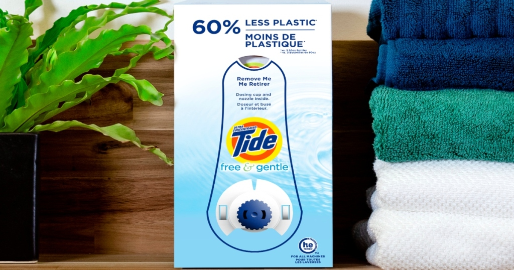 Tide free detergent in eco friendly box with a spout on a shelf next to a stack of folded towels