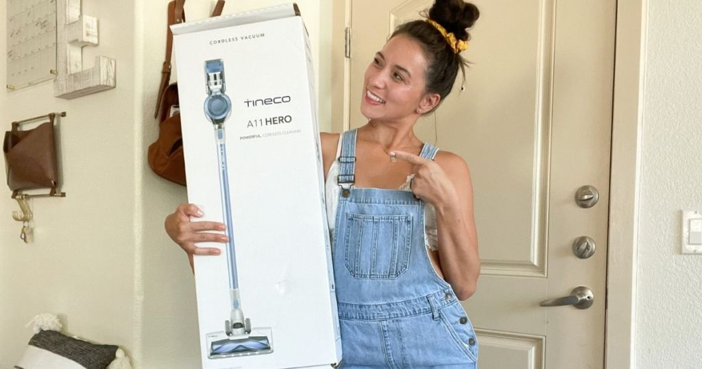 woman holding vacuum box and pointing at it