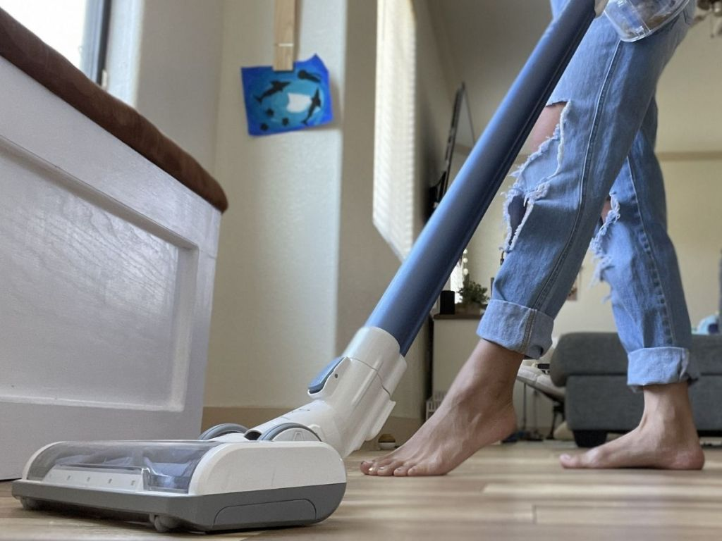 woman using vacuum on hardwood floors