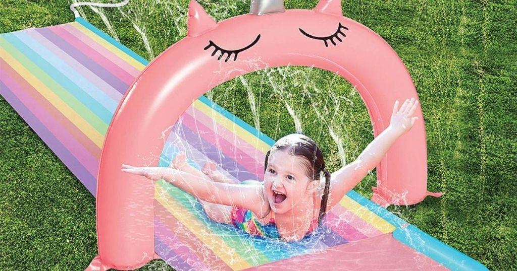 girl sliding down rainbow unicorn slip and splash spinkler