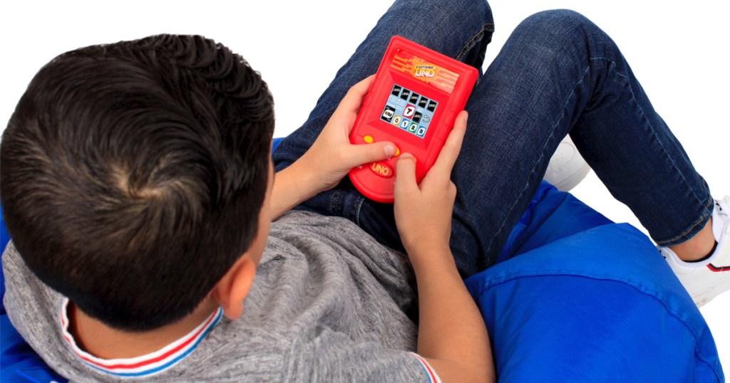 Kid playing uno handheld game