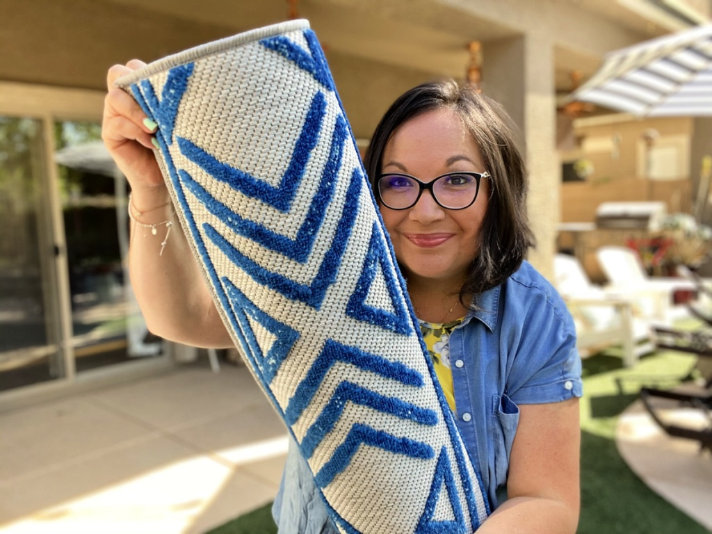 woman holding a blue and white outdoor rug