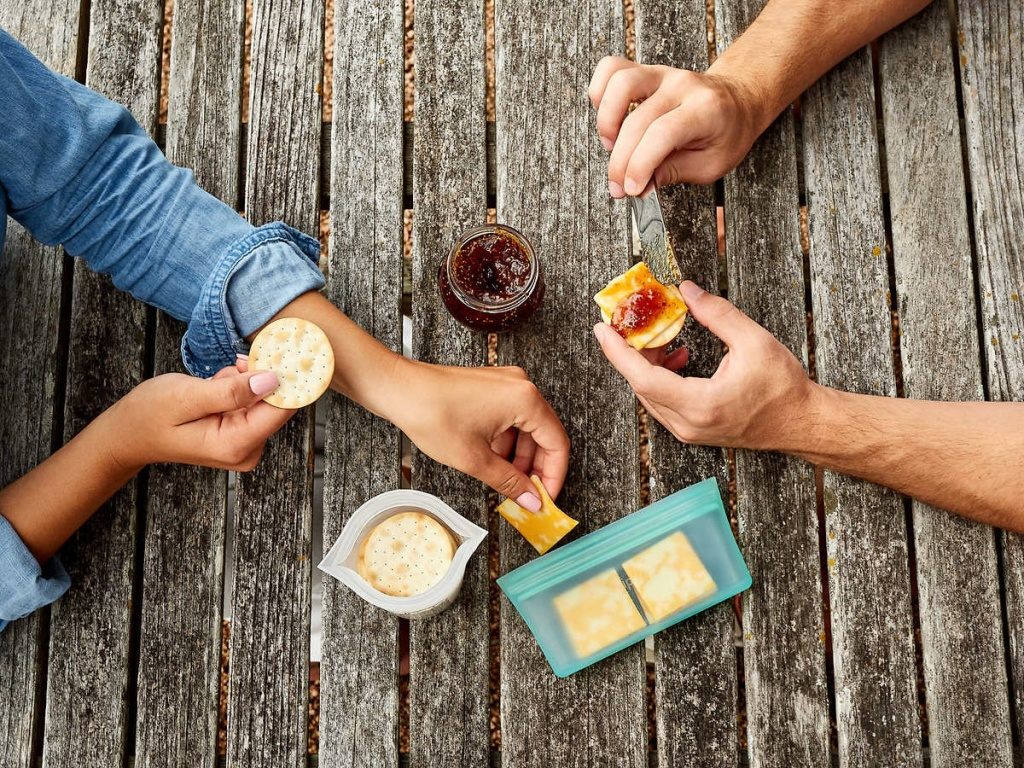 picnic table top with people eating snacks on it