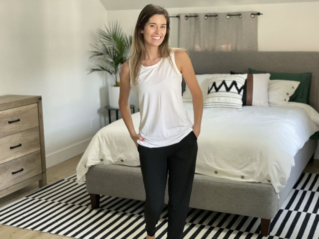 woman standing in a bedroom by a bed