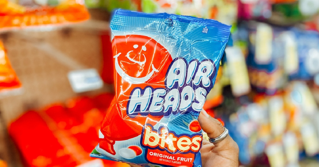 Hand holding up Air Heads candy bag