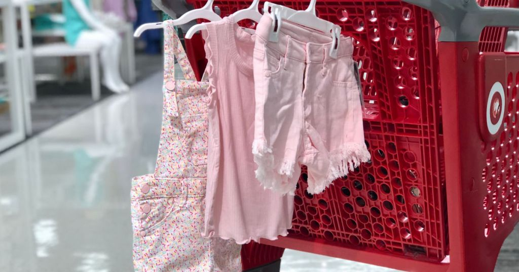 pink clothing hanging from red cart